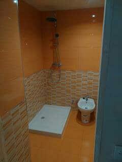 bano con plato de ducha de porcelana y suelo ceramico naranja