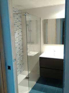 bano con plato de ducha mampara y mueble de lavabo y suelo azul hidraulico