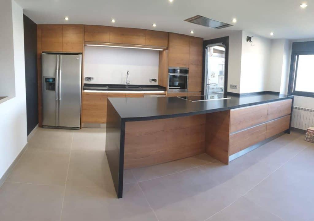 cocina remodelada con suelo porcelanico roca de 90x90 con isla de piedra de granito en negro con luces led y extractor integrado