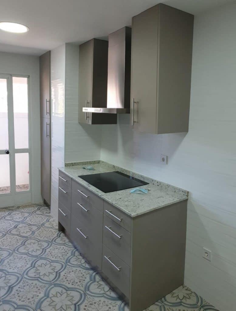 reforma de cocina con suelo hidraulico de dibujo de masico con encimera de granito y mobiliario de color gris mate